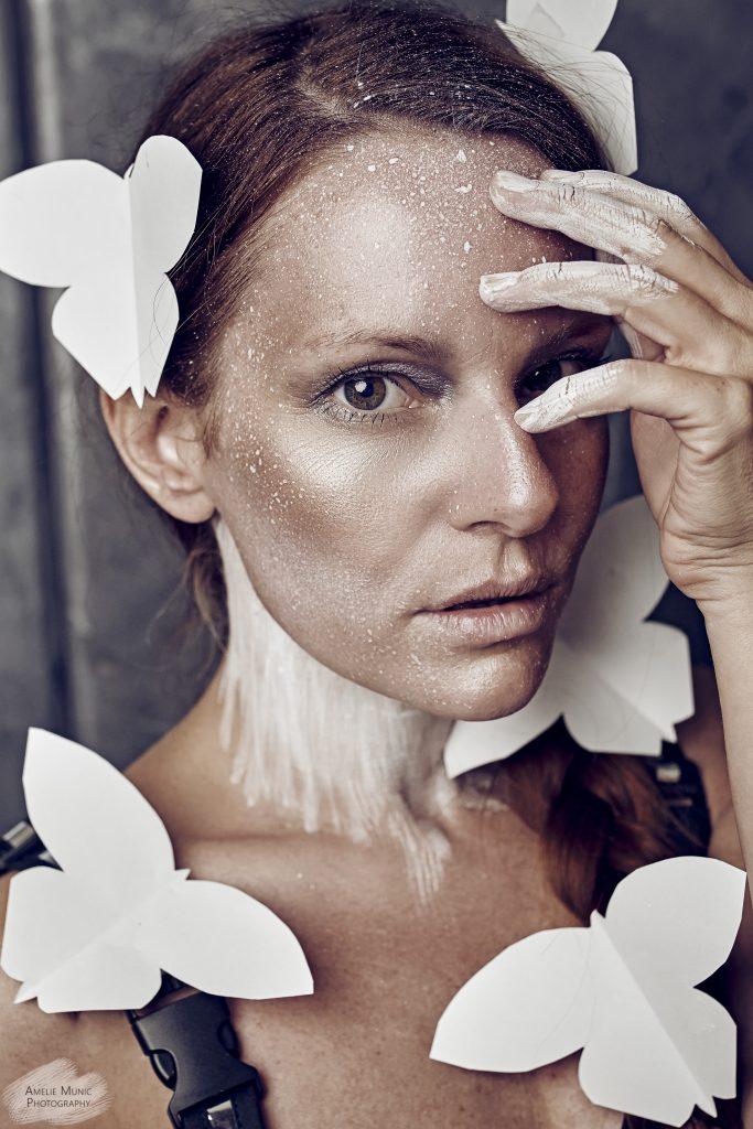 Portrait-einer-frau-mit-weißen-papier-schmetterlingen
